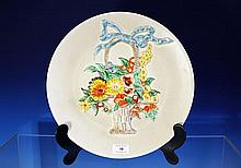 A Clarice Cliff charger beige glazed body with relief moulding depicting a floral basket with ribbon bow to handle,