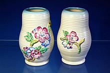 A pair of Clarice Cliff vases of ribbed baluster form, floral decoration in relief, raised Newport signature, 6in. (15.2cm.) high. (2)