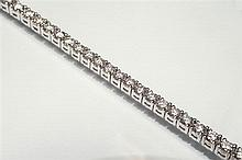 An 18ct white gold and diamond tennis bracelet set with sixty-two round brilliant cut diamonds, total diamond weight 5 carats,