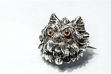 An antique silver plated dog brooch in the form of a terrier's head, set with amber glass eyes, Continental, 2.1cm. high.