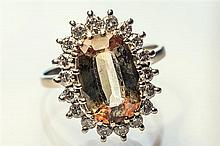 An 18ct white gold, andalucite and diamond cluster ring the cental cushion cut andalucite, approx. 12 x 8mm.,