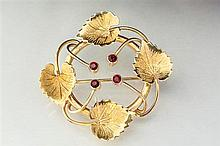 An 18ct gold and garnet foliate brooch the swirled vine form frame issuing four leaves,