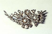 A Victorian gold, silver, diamond and seed pearl floral spray brooch designed as a ribbon tied floral and foliate spray,