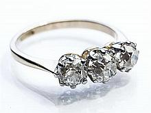 An 18ct gold and platinum three stone diamond ring the rhodium plated yellow gold ring with three claw set old cut diamonds totallin...