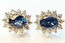A pair of 18ct yellow gold sapphire and diamond cluster earrings the oval cut sapphires, totalling 3.07 carats,