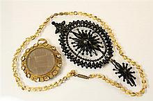 A Victorian jet style pendant of pierced oval form, centred with a flower and with a smaller conforming flowerhead to the bale,