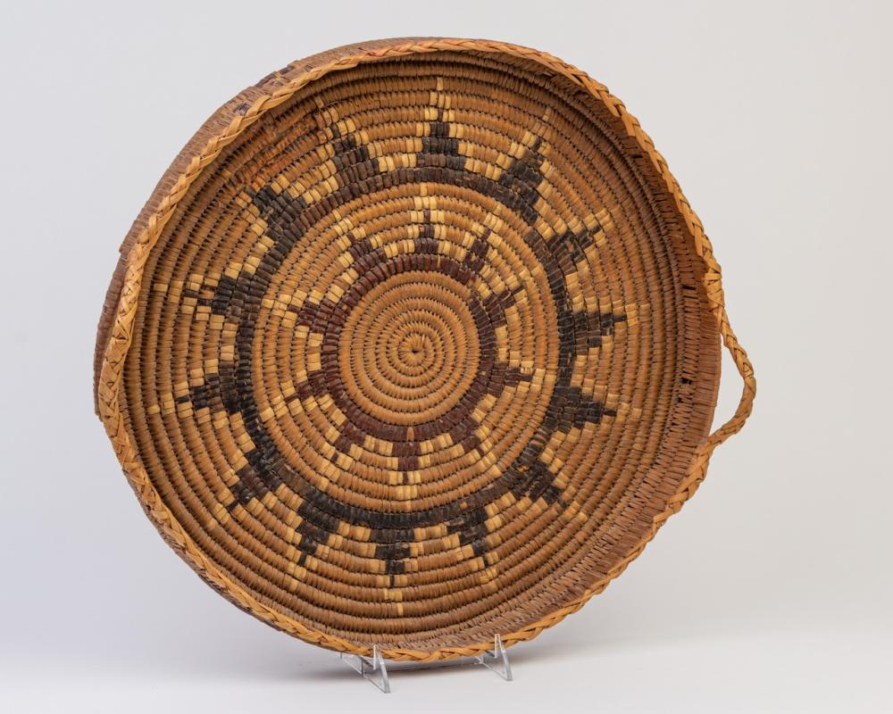 A round Salish cedar root serving tray, 18 in. (38 cm) d.