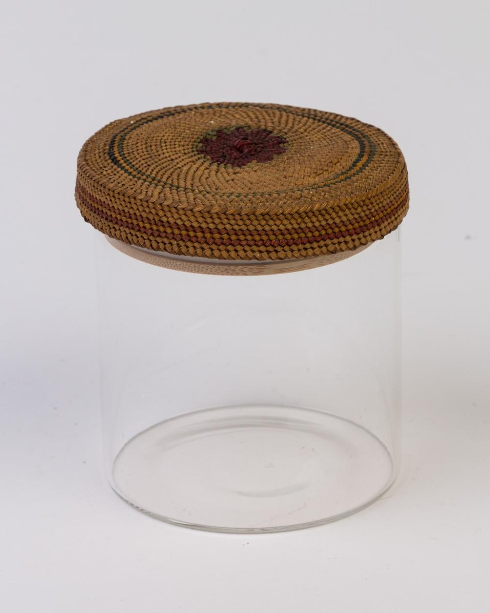 A glass jar with a Nuu-chah-nulth woven grass Iid.