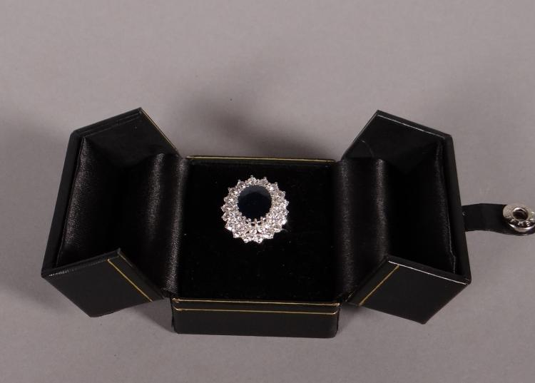Jewelry: 18k White gold ring set with a sapphire entourage of brilliant 2x18