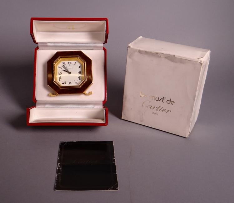 Watchmaking: Clock CARTIER in gold metal and red lacquer with alarm clock