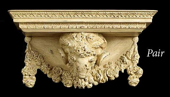 """Large Pair of Edwardian Carved and White-Painted Wooden Bracket Shelves, in the style of Robert Adam (English, 1728-1792), each oblong shelf supported on a garlanded ram's masque, the painted white finish tastefully aged and distressed, h. 9"""", w."""