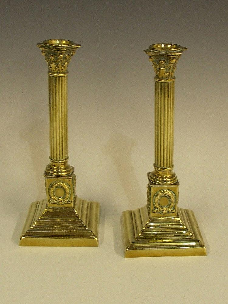 A pair of Corinthian capped columnar brass table
