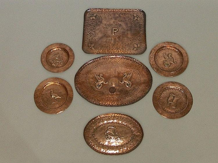 Seven copper trays and dishes each embossed to the