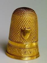 A yellow gold thimble of conventional design with vacant shield shaped cart
