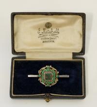 A 19th Century gilt white metal brooch centred on a cushion cut green stone
