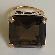 A 9ct gold smoky quartz dress ring the claw set cushion cut stone in deep p