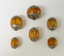 Six various silver coloured metal mounted amber beads, various shapes and s