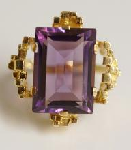 A 14ct yellow gold amethyst ring the claw set baguette cut stone in a recta