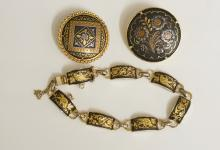 Two circular gilt metal inlaid brooches, 2.8cm diameter and smaller; a gilt