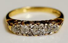 A five stone diamond ring, pavé set with scroll cast shoulder, 14ct yellow