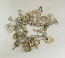 A silver charm bracelet of flattened curb links hung 18 charms, 69gms