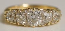 A five stone diamond ring the graduated oval stones within a scroll cast fr