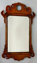 A George II style walnut fretted frame wall mirror, the shaped top pierced