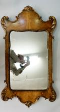 A George II style parcel gilt walnut wall mirror of shaped outline with car