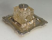 An Edwardian silver plated inkwell, the square glass well with sides cut wi