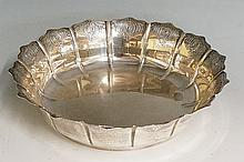 A silver dish, the petal form scalloped sides chased with a repeating scrol
