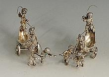 A pair of 19th Century Austrian? silver salts in the forms of cherubs drivi