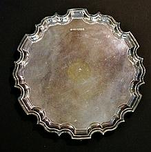 A plain silver salver with pie crust rim, three ball and claw feet, by Carr