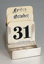 A silver perpetual desk calendar, the plain body with demi-lune pen rest to