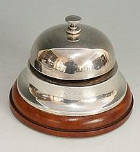 A silver desk or counter bell, twist action button to top, conventional dom