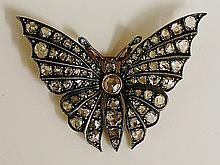 A gold coloured metal diamond set butterfly brooch the head and body with r