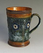 A Doulton pint mug or tankard, the body decorated with floral medallions on
