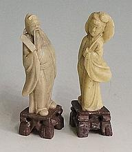 A pair of green soapstone figures of sages on brown soapstone bases, 10cm h