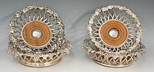 A good set of four silver plated wine coasters, comprising: two large and t
