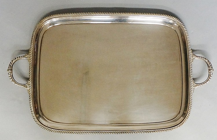 A large silver plated two handled tray with gadrooned rim, plain body, the