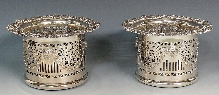 A pair of silver plated bottle coasters, the bodies pierced with scrolls, b