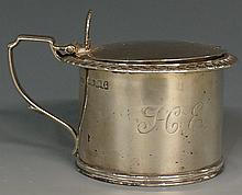 A George III silver mustard pot, the hinged lid decorated with concentric c