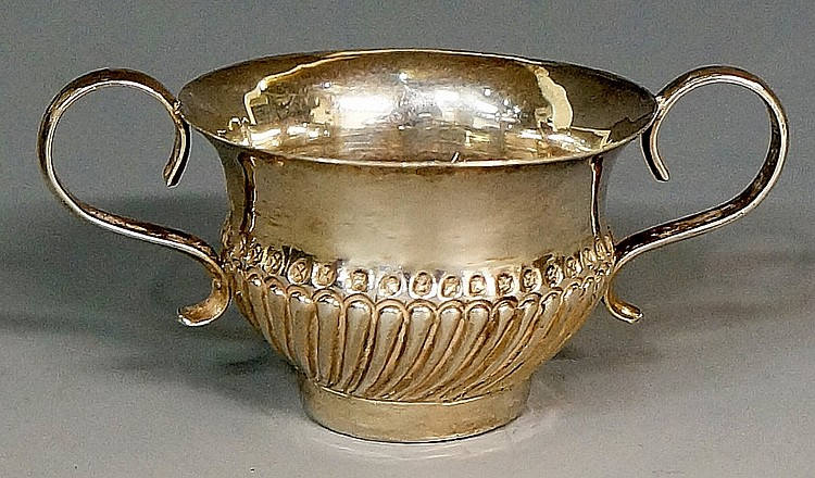 A miniature silver coloured metal porringer, spirally lobed lower body with