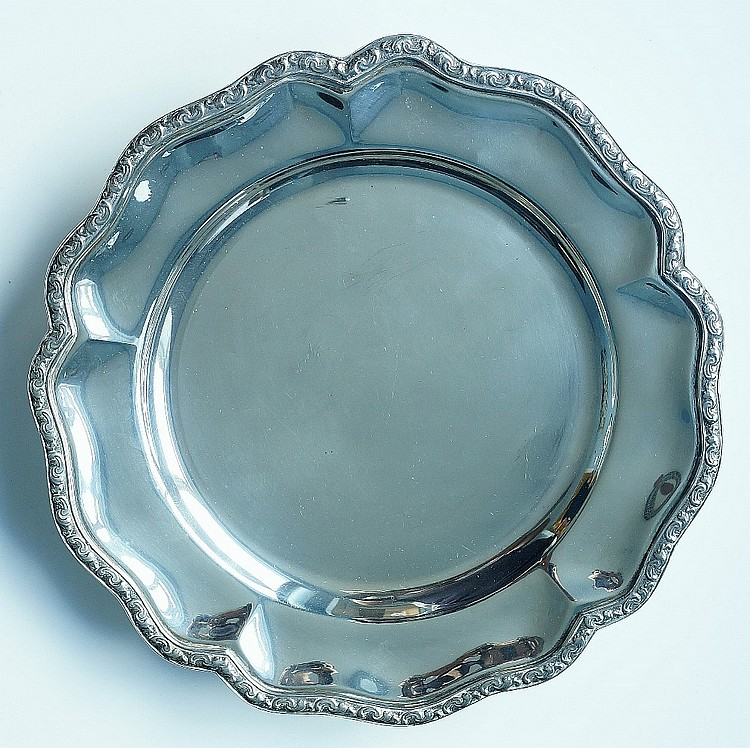 A silver salver, the petal shaped rim with applied scroll border, plain bod