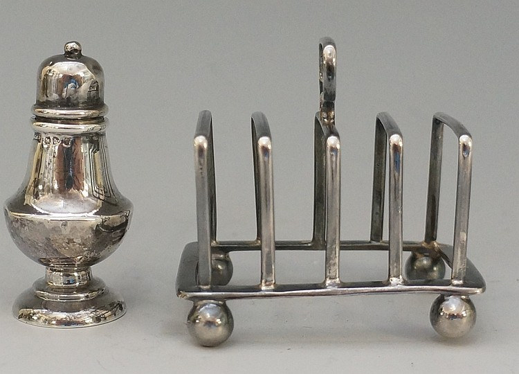 A miniature silver toast rack of simple angular form with plain ball feet,