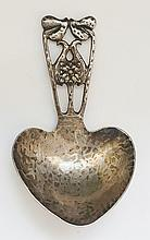 A silver Arts and Crafts caddy spoon, the handle in the from of stylised le