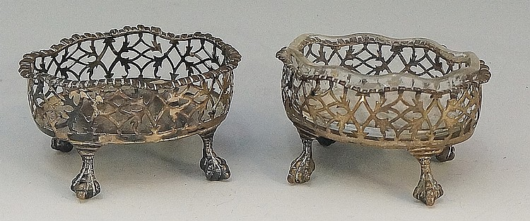 A pair of silver coloured metal salts, pierced bodies with gently ruffled r