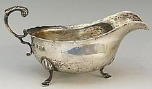 A silver sauce boat of conventional form, flying acanthus cast handle, thre