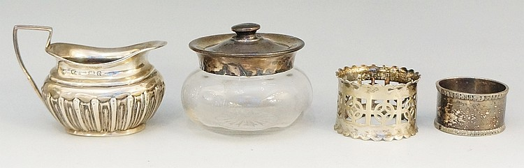 A selection of silver items to include: a cream jug with half gadrooned bod