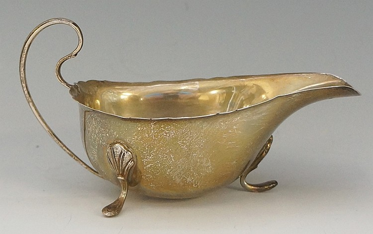 A silver sauce boat of conventional form, three stylised shell and hook fee