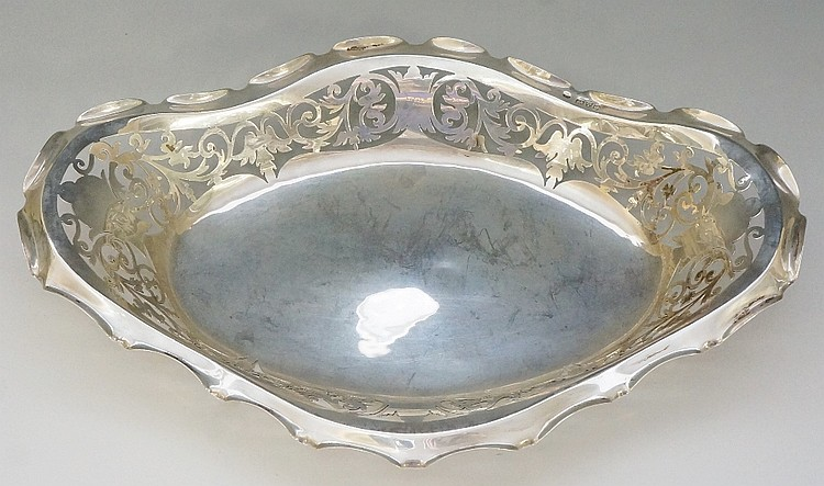 An Edwardian silver dish with pierced scrolling foliate sides and scalloped